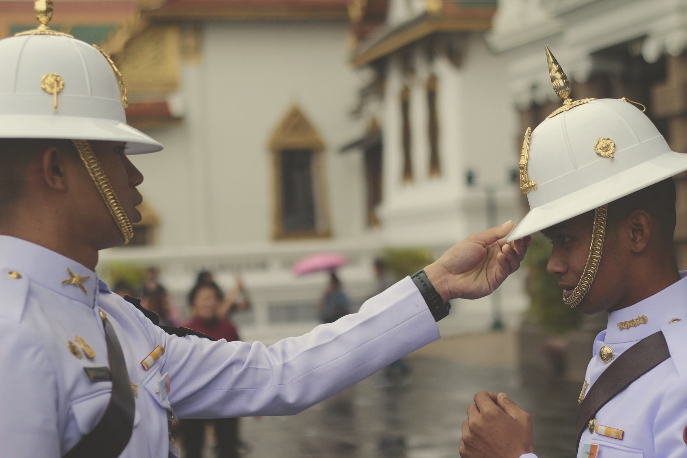 officer in white uniform touching man's white hat