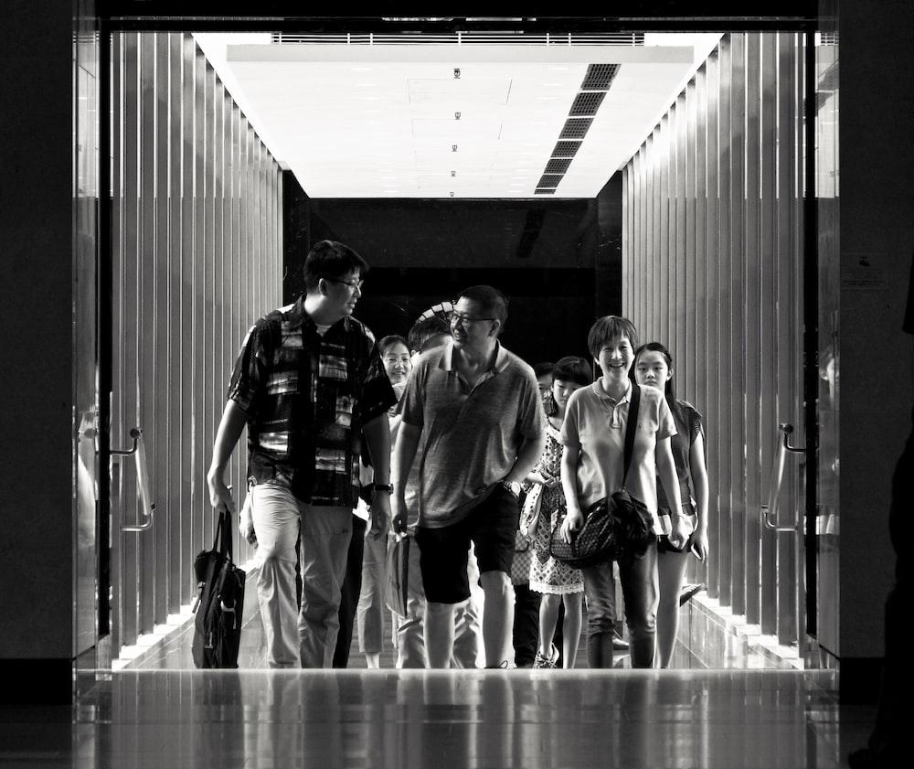 grayscale photography of people walking on hallway