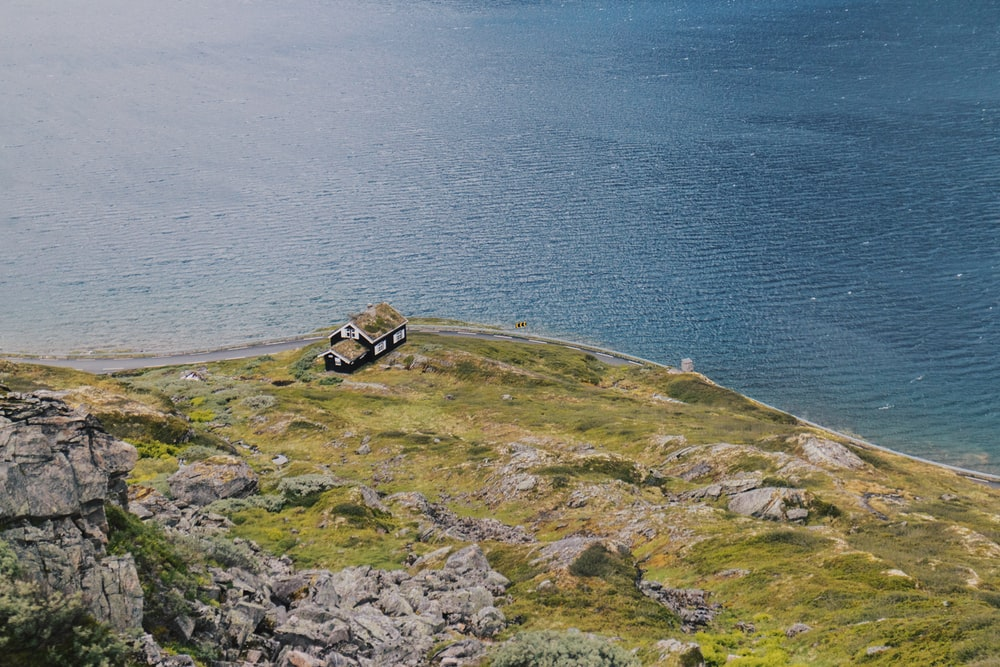 photo of house on cliff near body of water