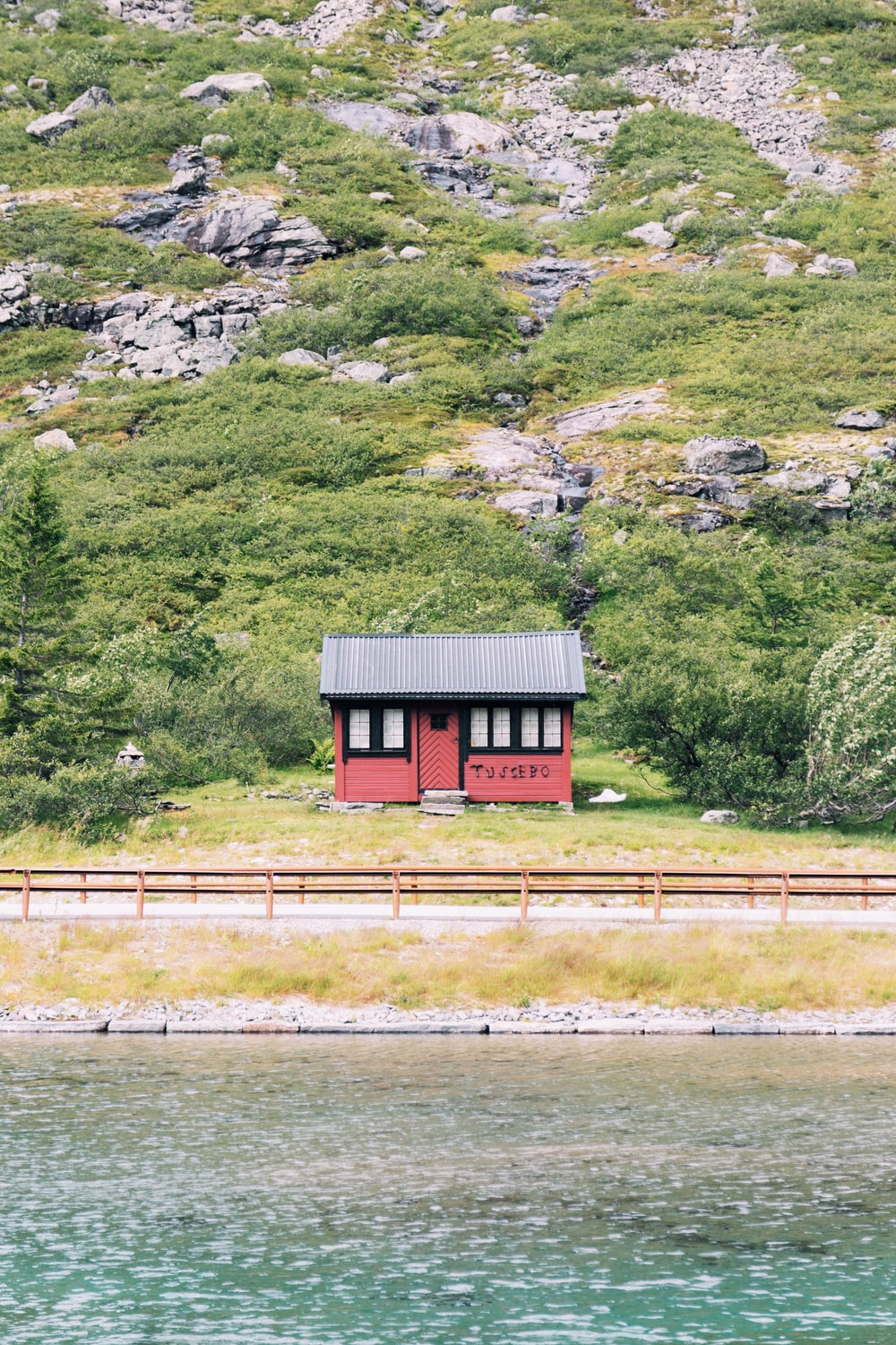 red and black wooden shack on hill near road