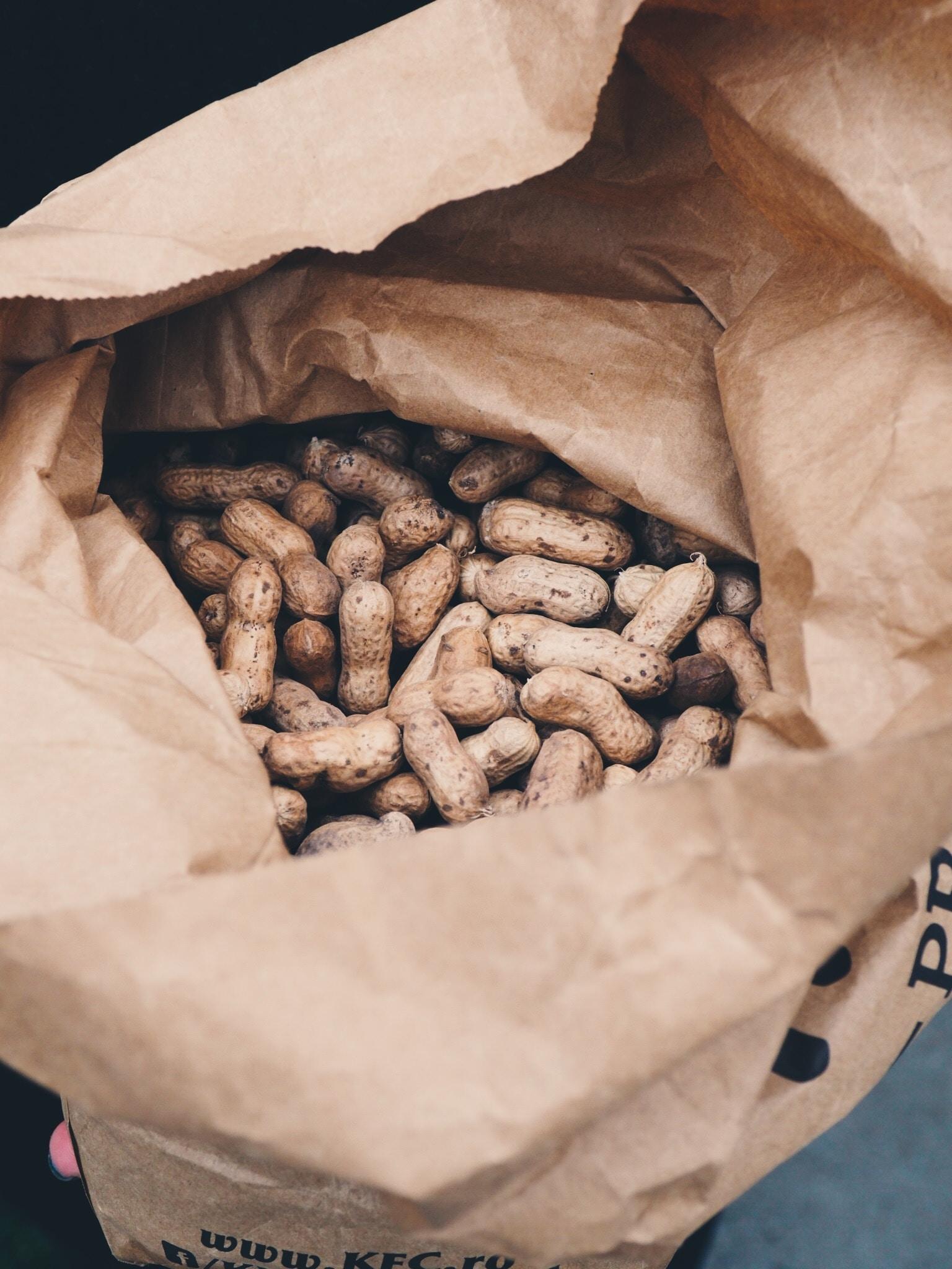 brown peanuts in brown opened paper bag