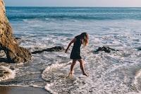 woman in black dress walking in seashore