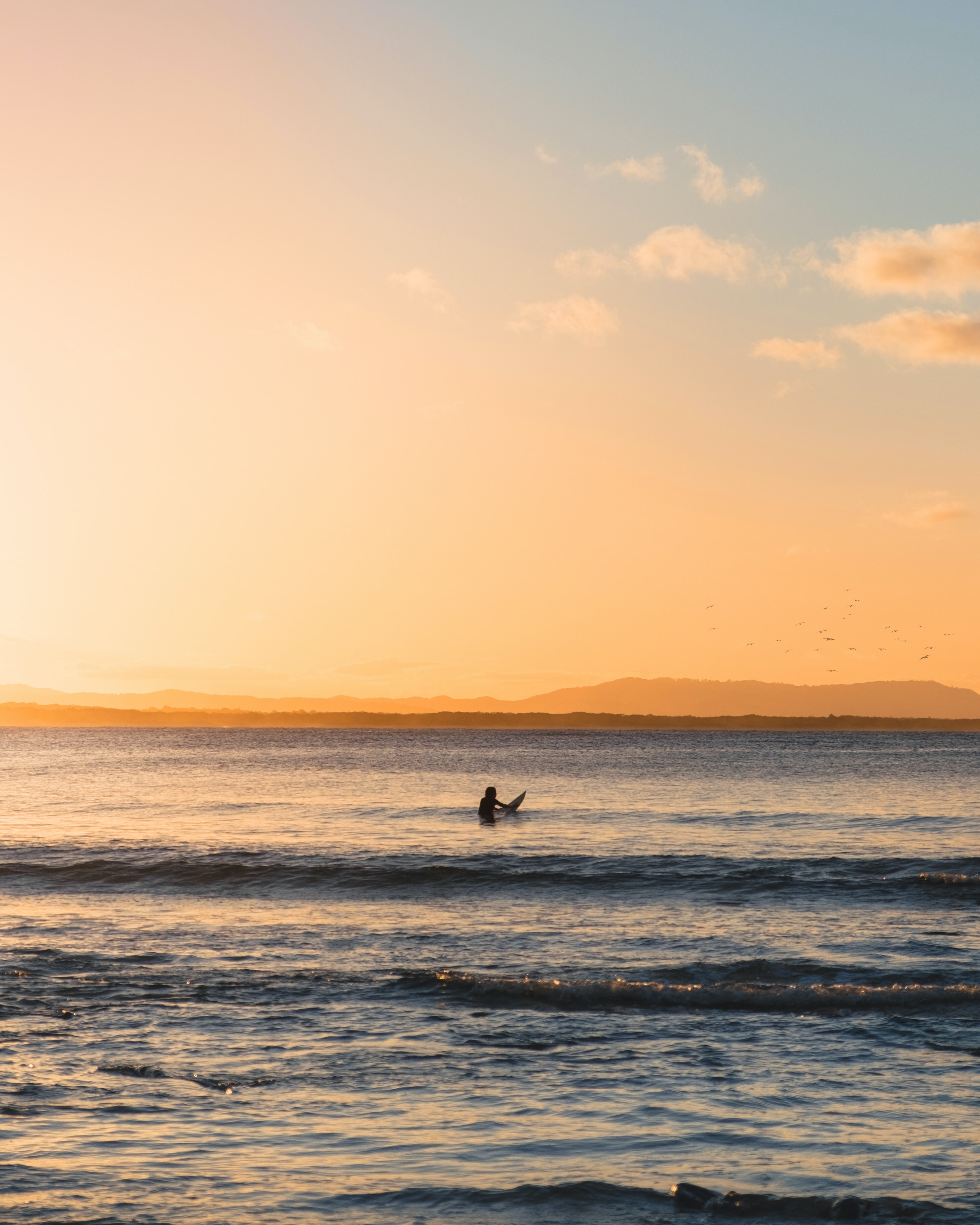 photo of person holding surfboard at the sea