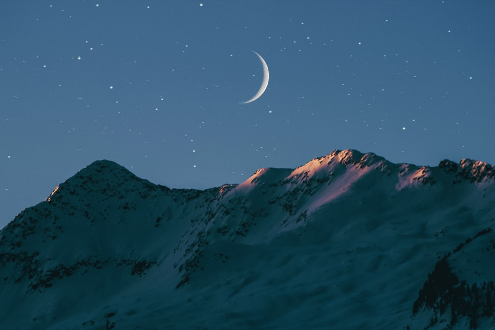crescent moon above mountain