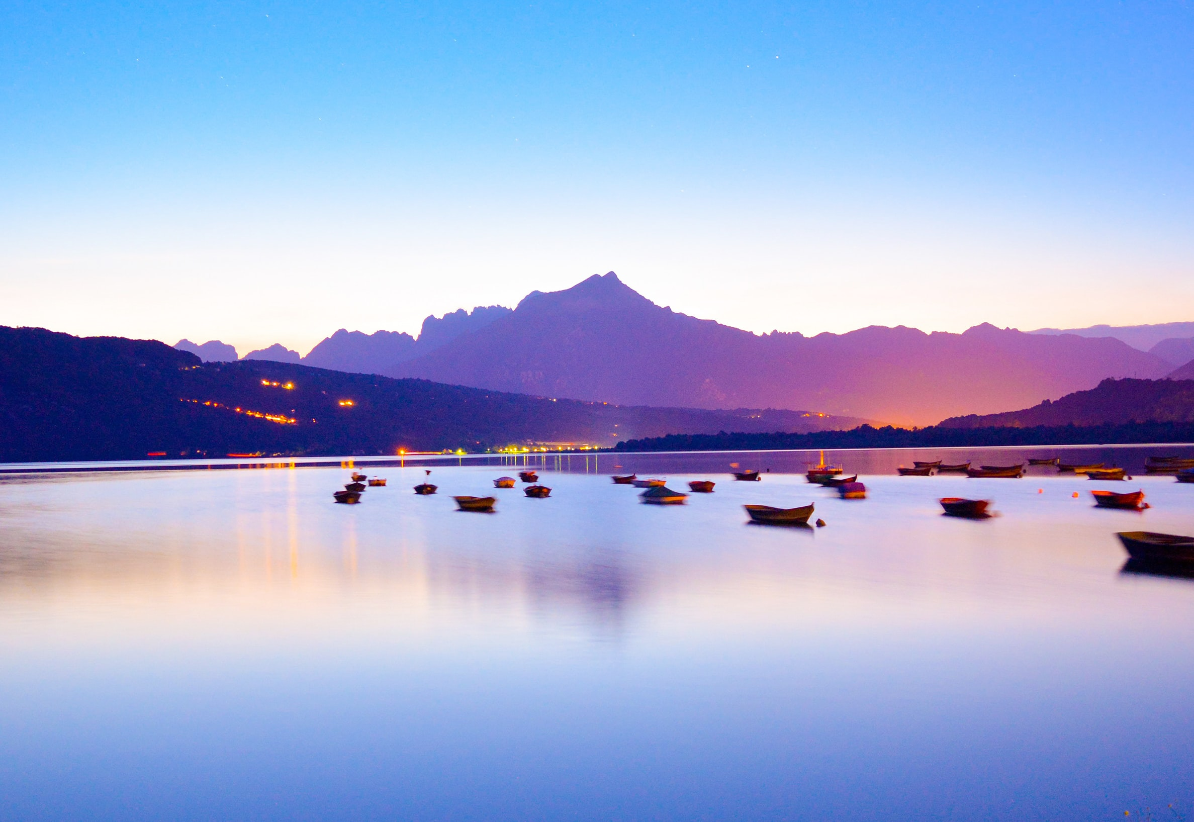 boats in body of water overlooking mountain