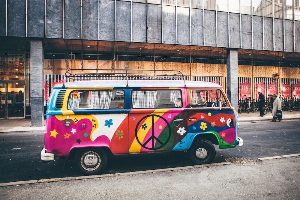 multicolored minivan parked on roadside near building