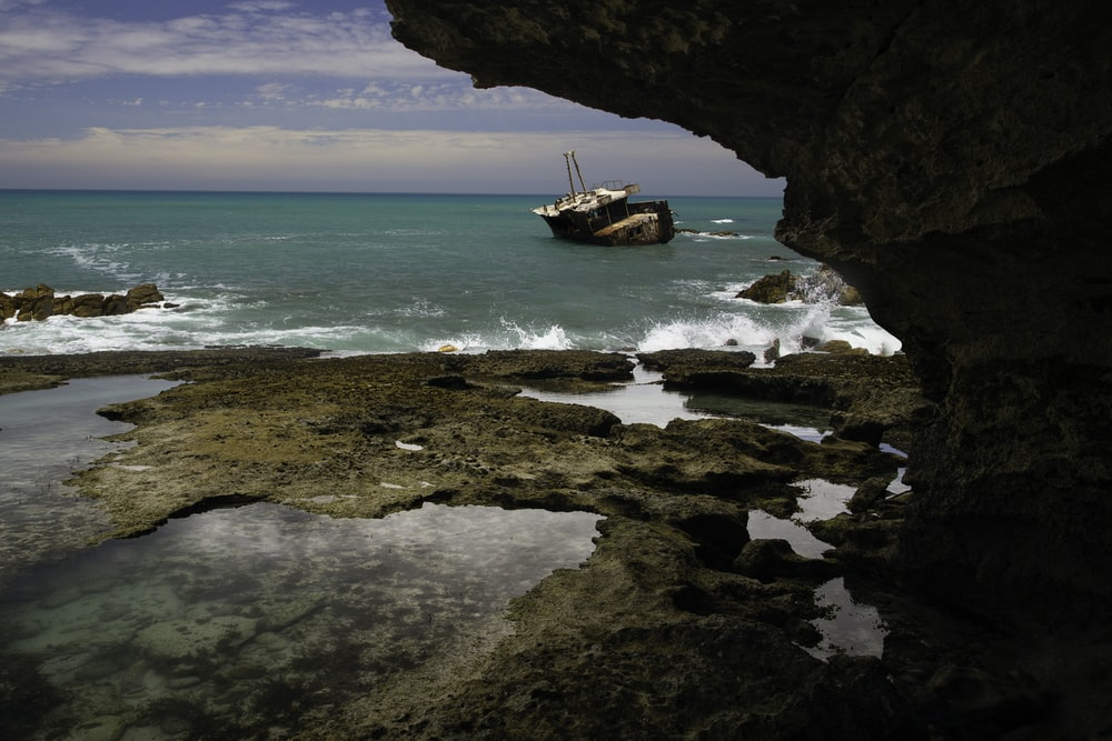 brown and white fishing vessel near rock formation