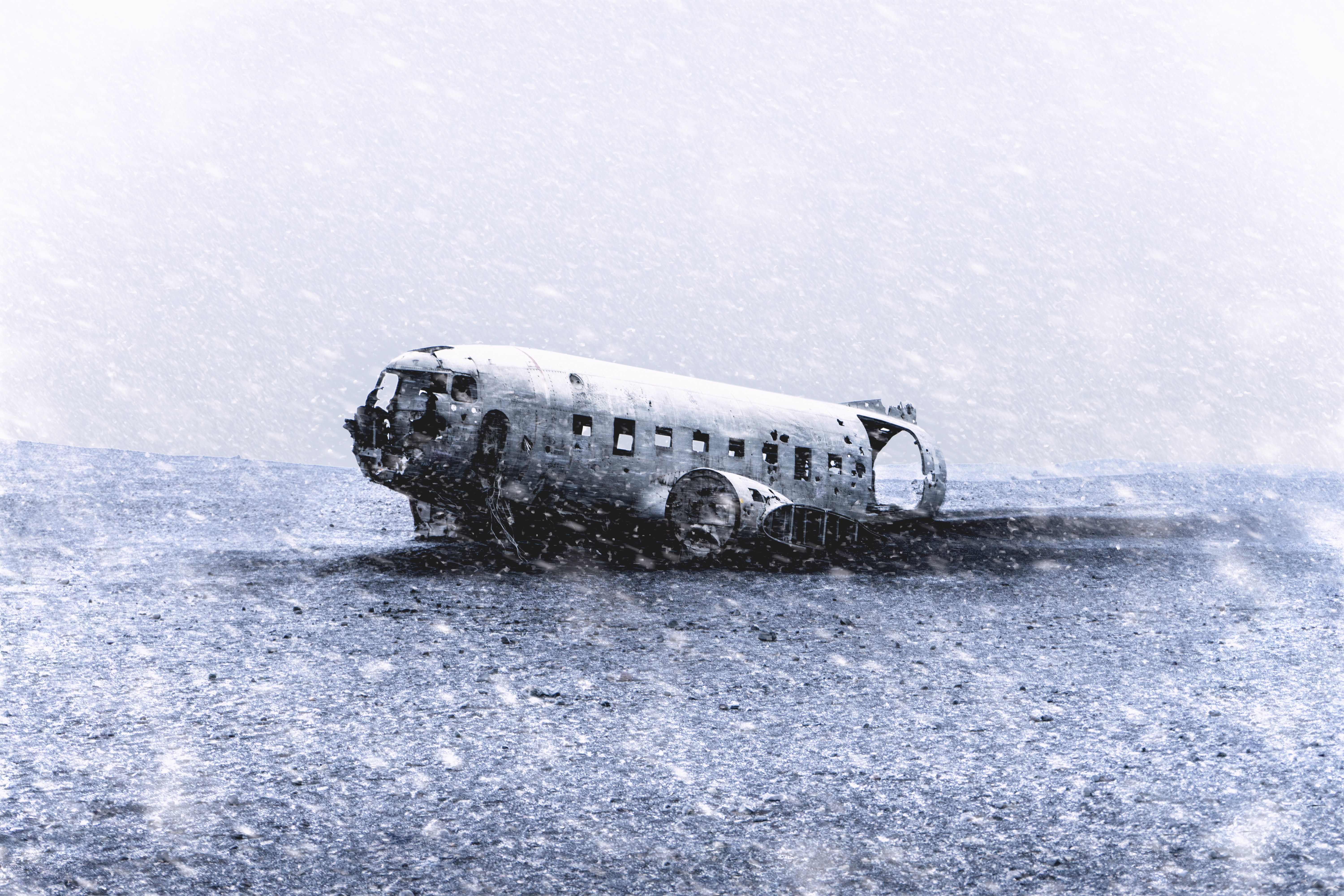 crashed airplane on sand grayscale photography