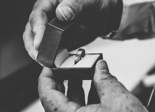 grayscale photography of person holding silver-colored ring in opened box