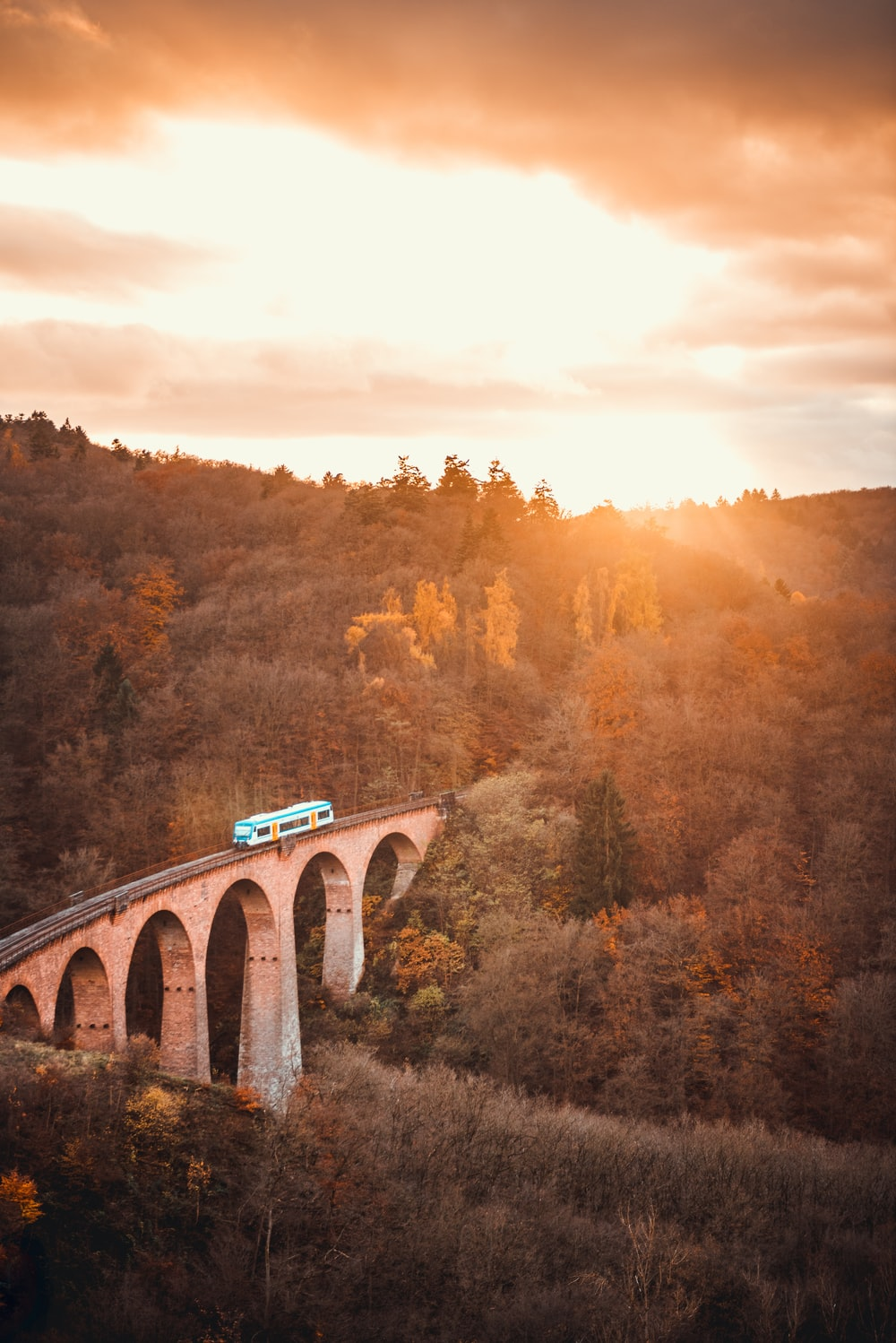 aerial view photography of train on bridge during sunset