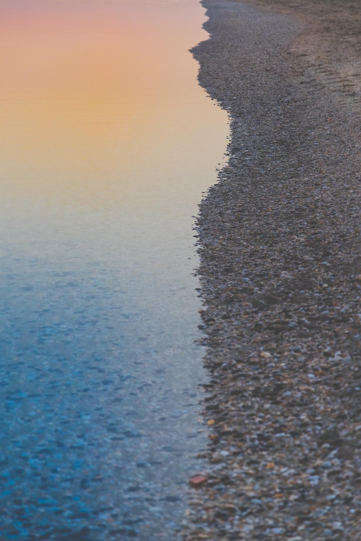 shore beside ocean during sunset