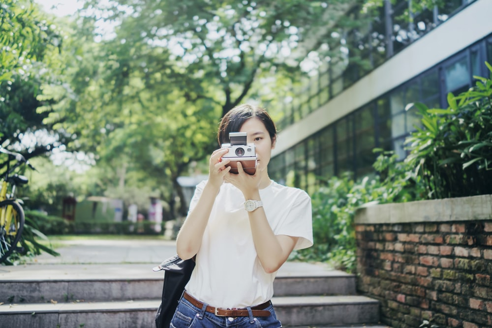 woman in white T-shirt using camera
