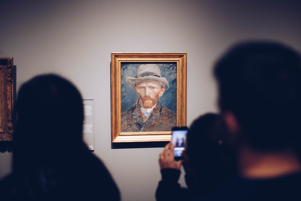 person taking picture of man wearing brown hat painting