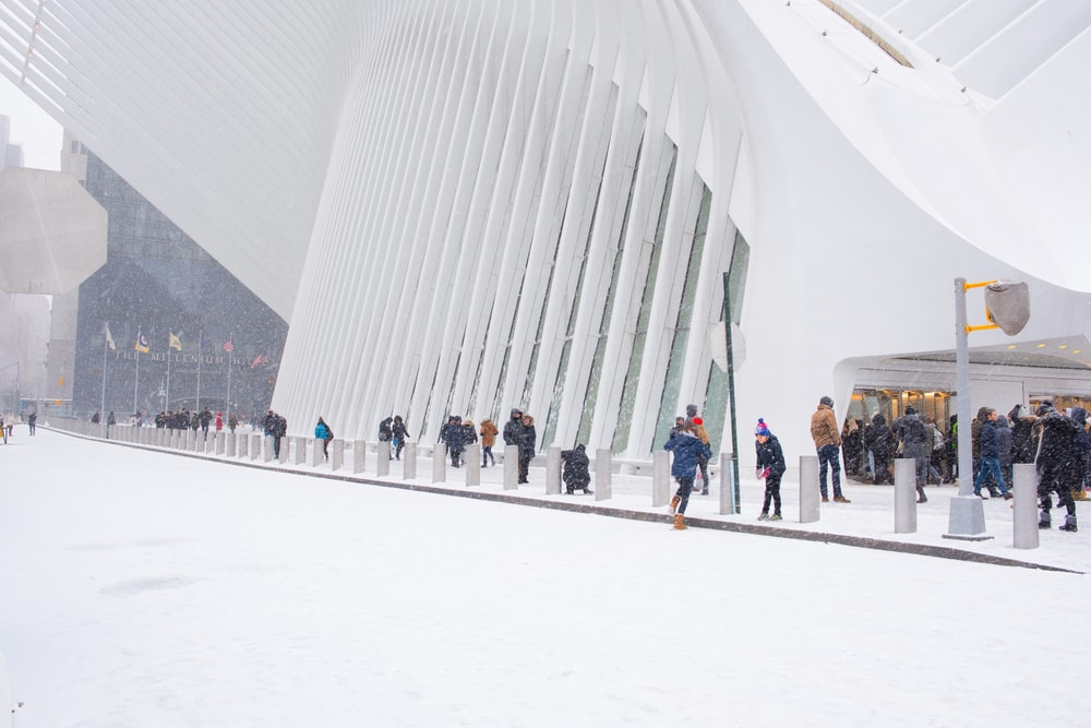 people near white concrete building with snows at daytime