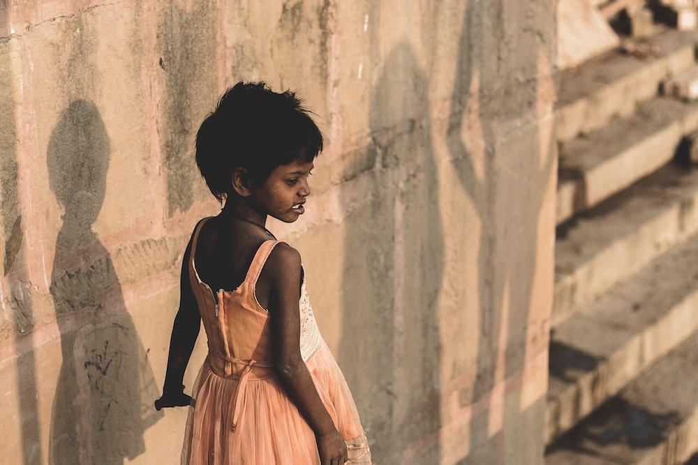 girl wearing beige sleeveless dress standing near wall