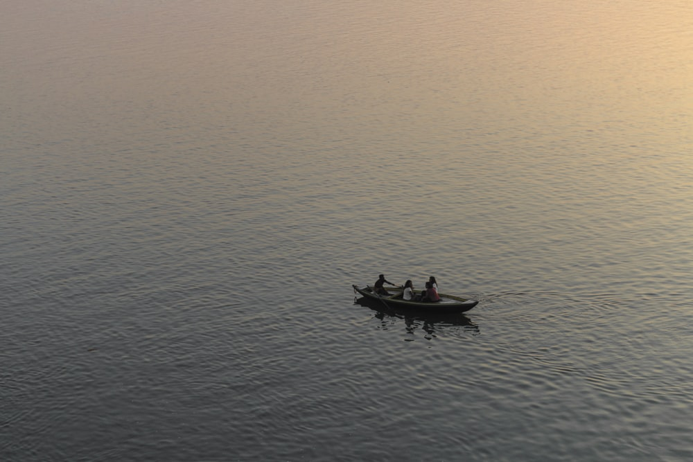 three person riding on boat surrounded by water during golden hour