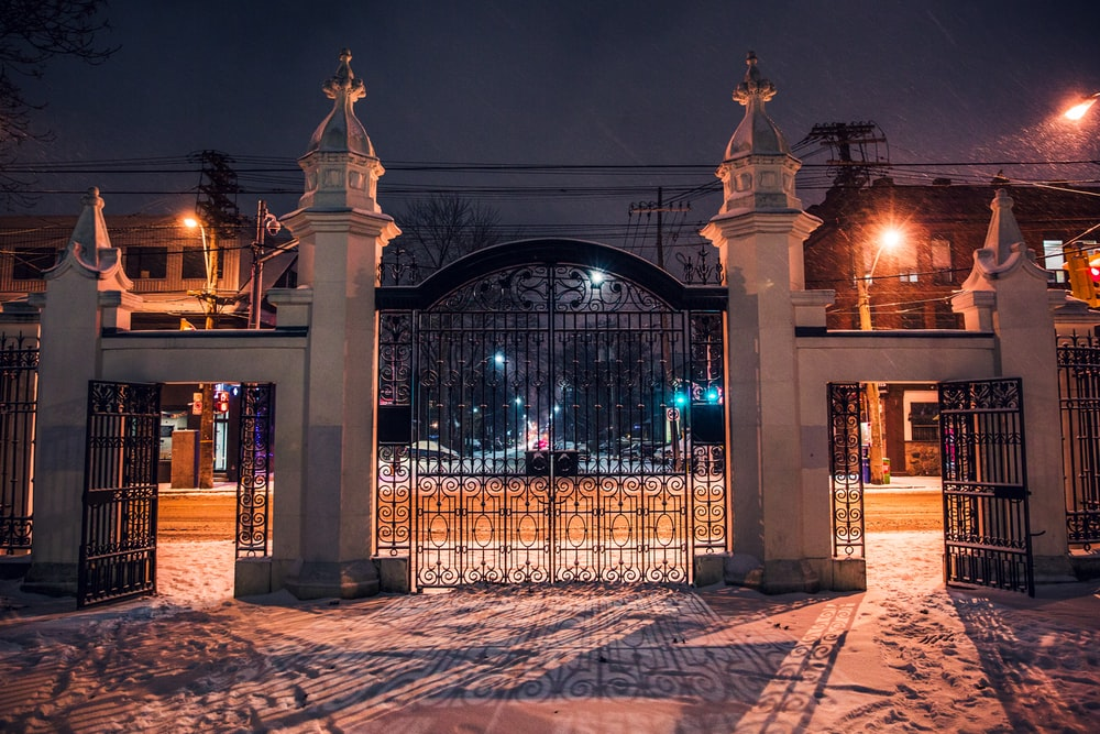 architectural photography of black metal and concrete gate