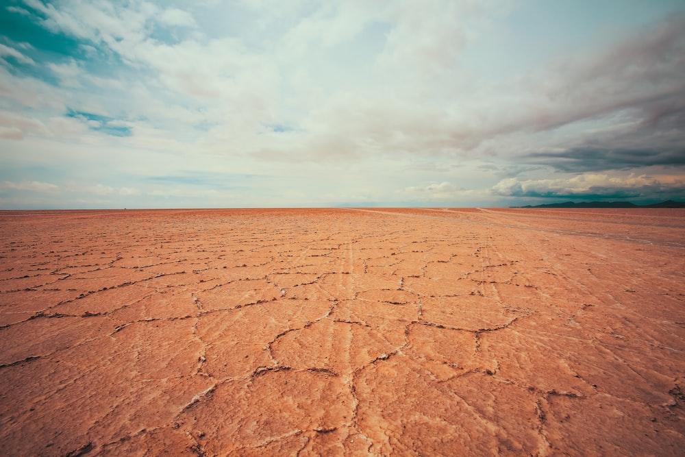 empty desert under white cloudy sky at daytime