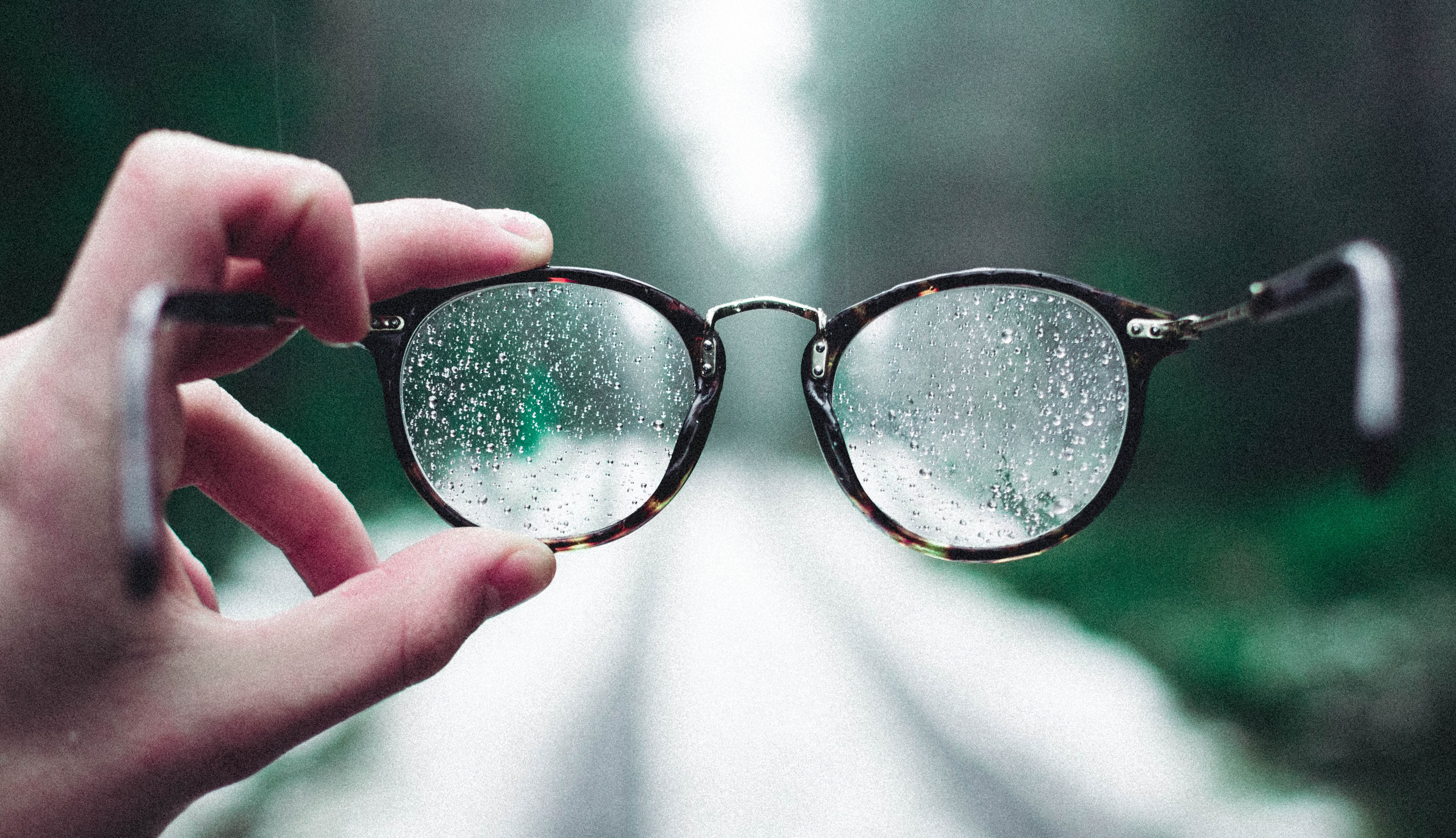 person holding eyeglasses with water droplets