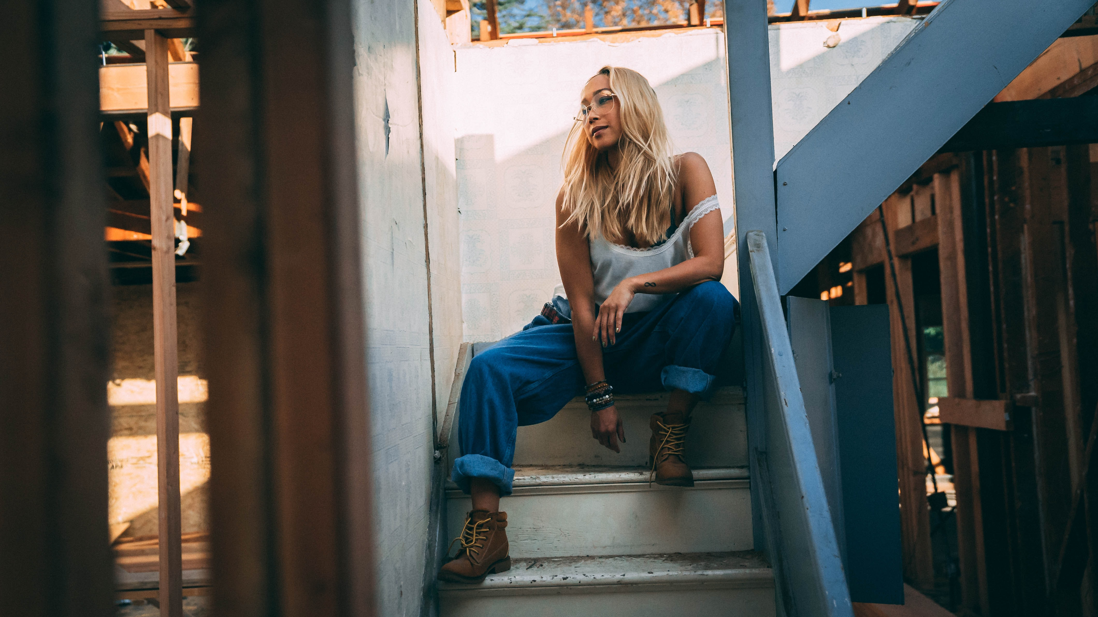 woman in blue tank top and blue denim pants sitting on stairs