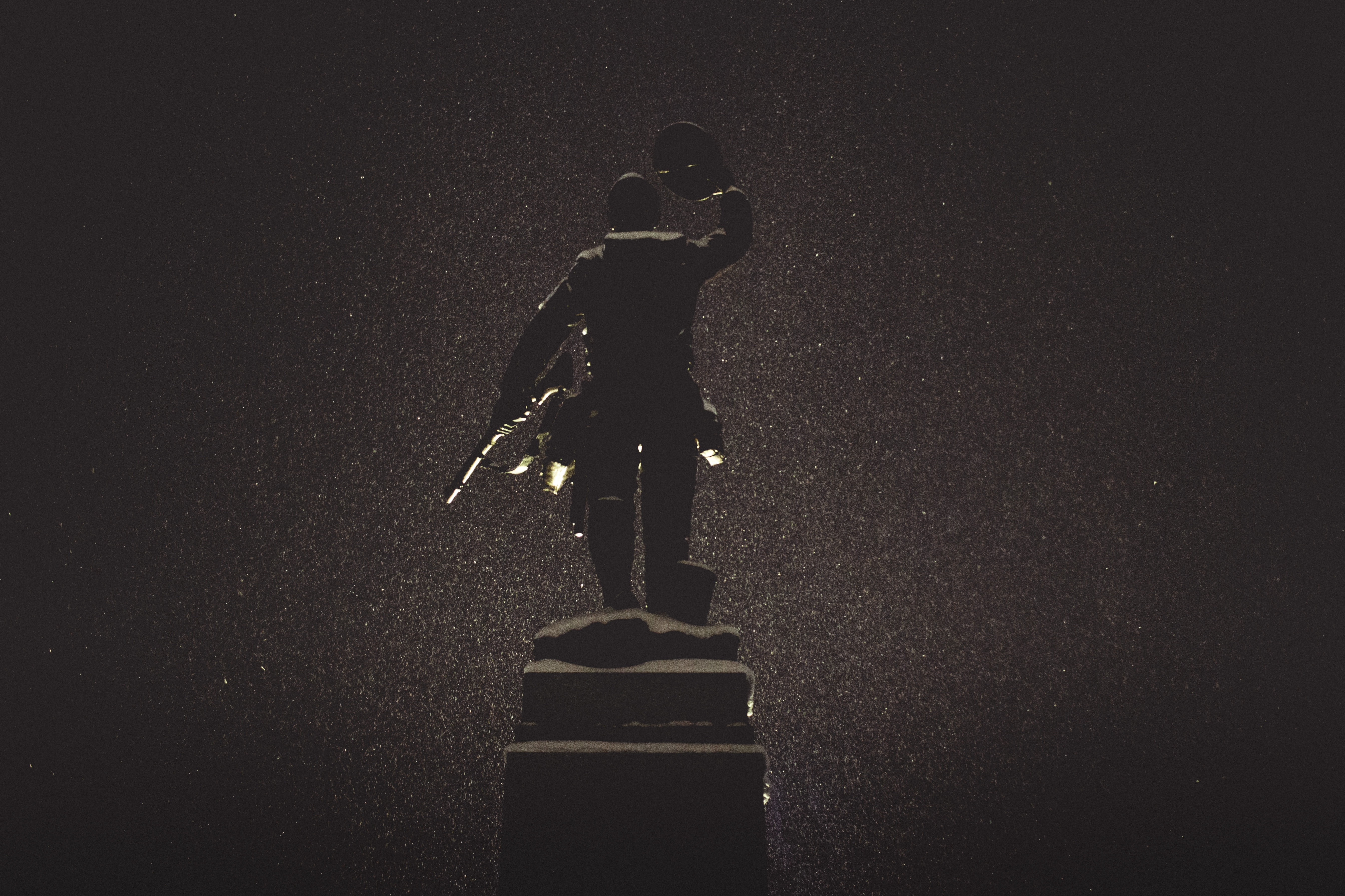 silhouette of statue against black background
