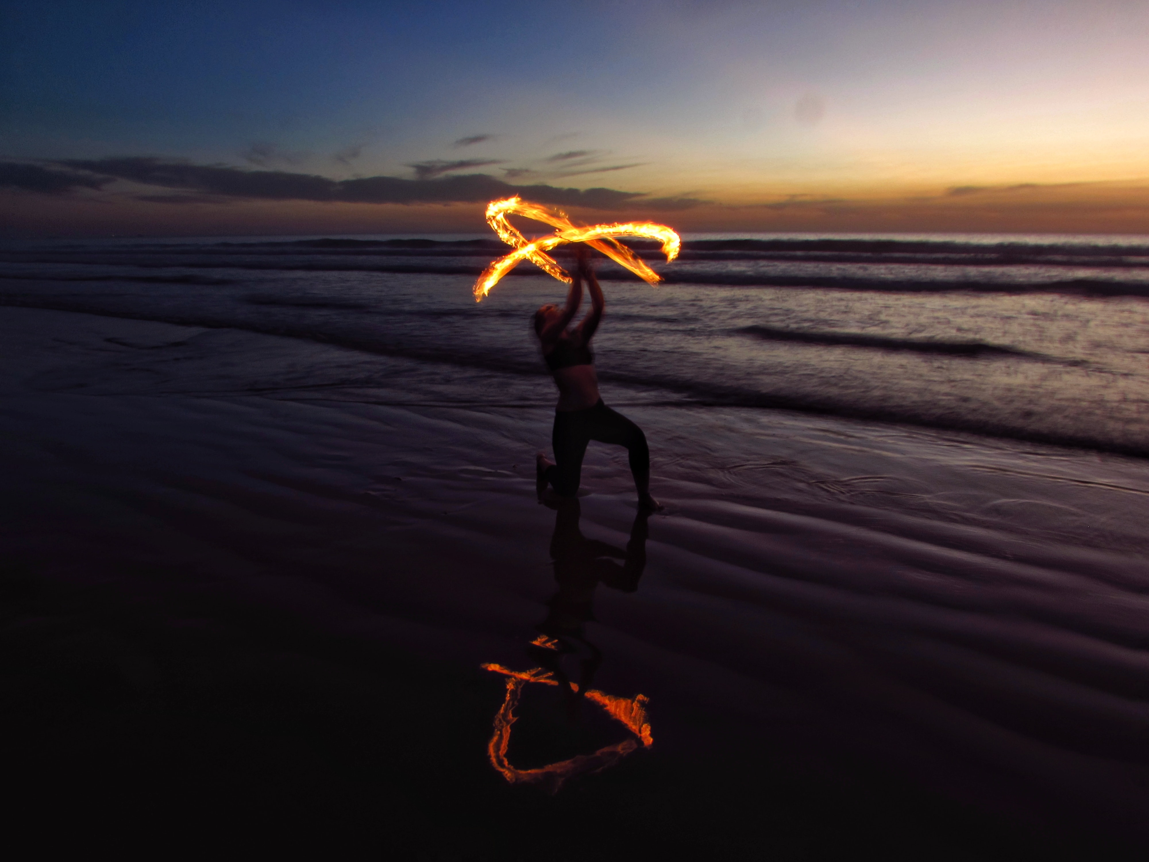 person doing fire dancing on seashore