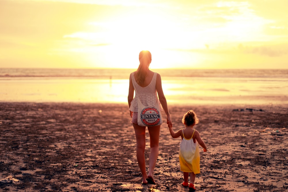 woman and child facing towards sunset