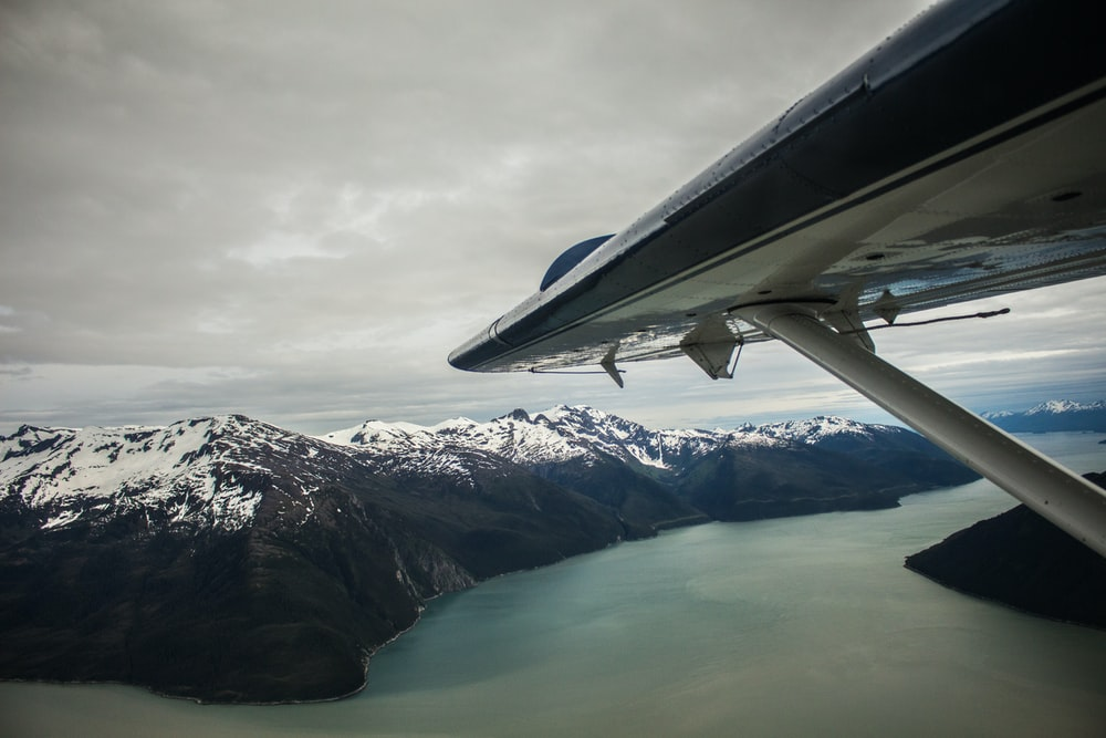 aerial view photography of airplane wing above snow mountain