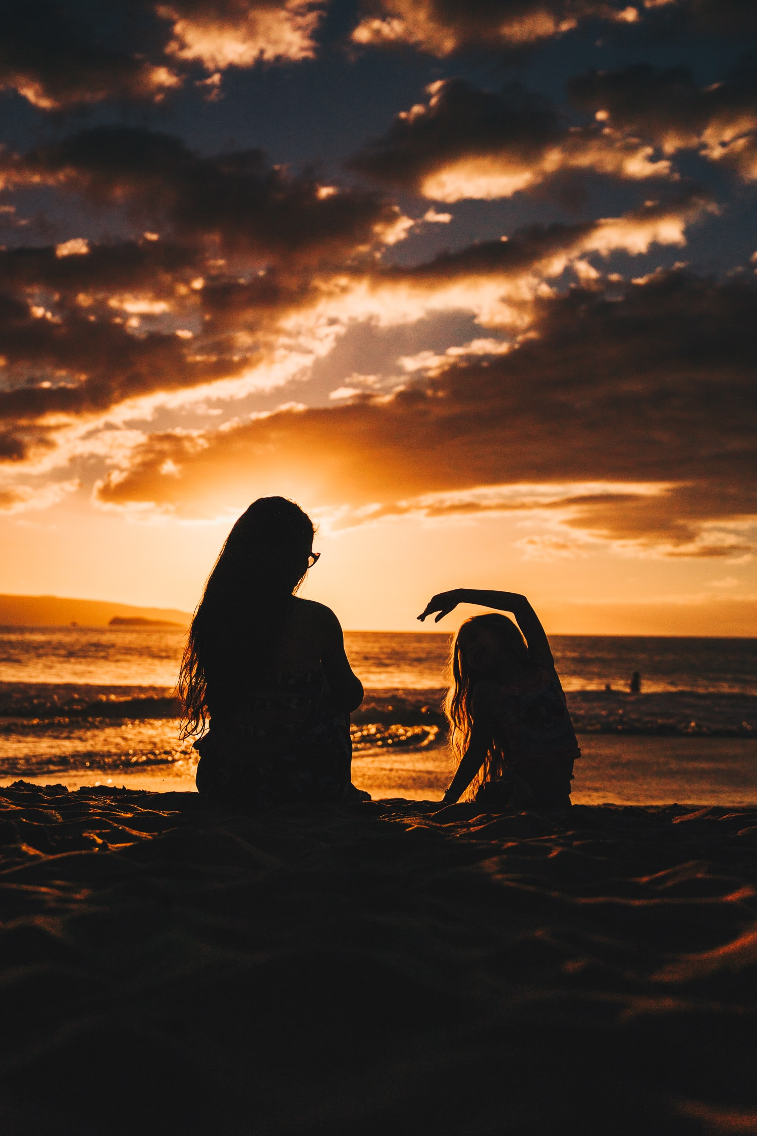 silhouette photo of woman and girl on shoreline
