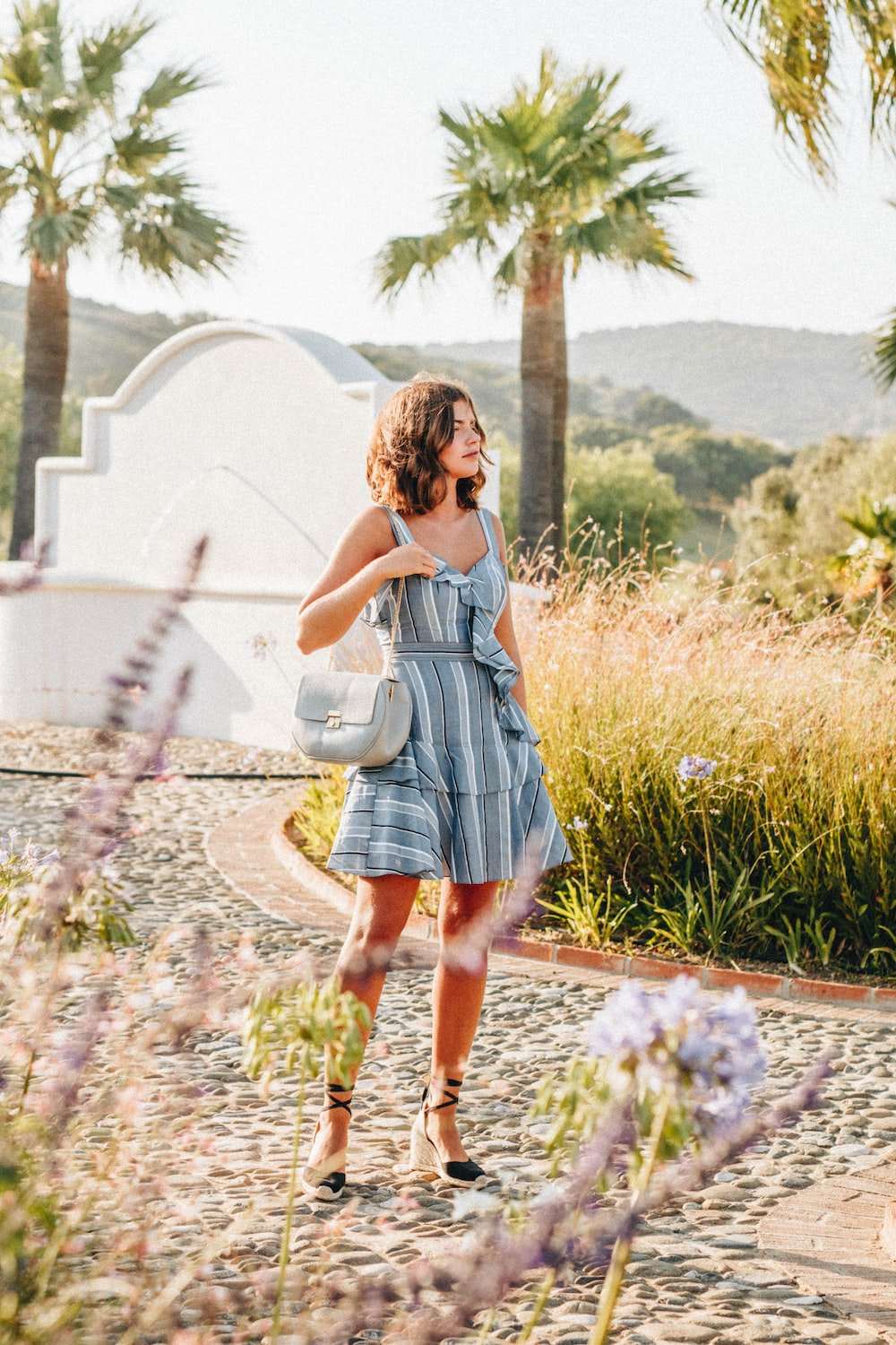 woman in gray sundress carrying sling bag in middle of pathway during daytime