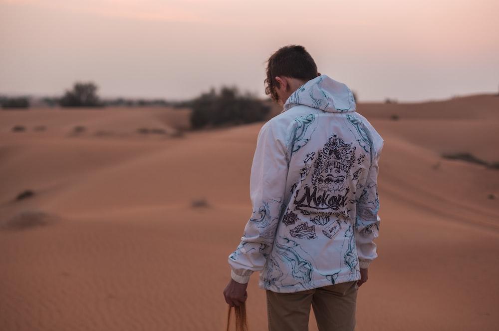 man standing on desert holding sand during daytime