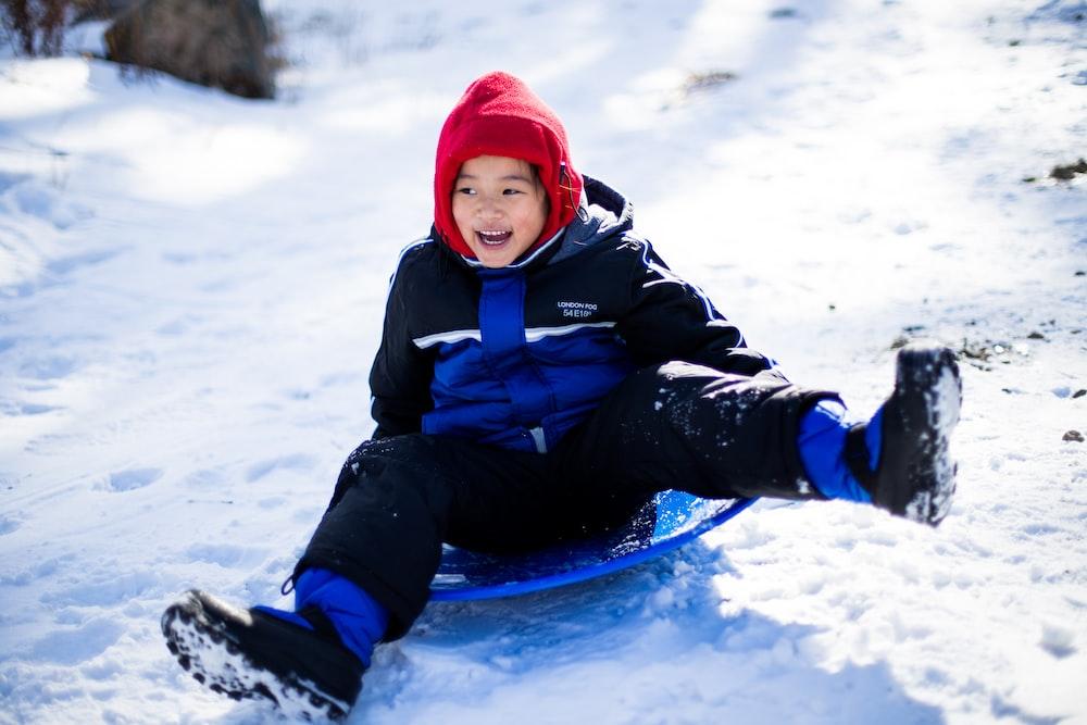 boy riding blue sled