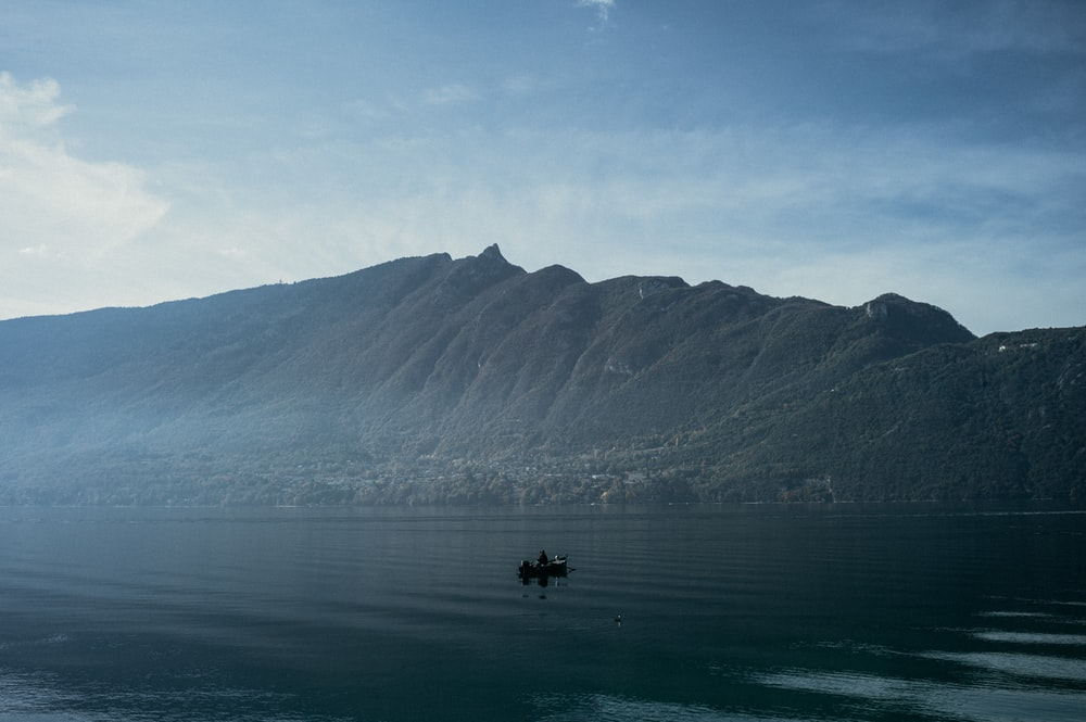 person on board on body of water near mountain during daytime