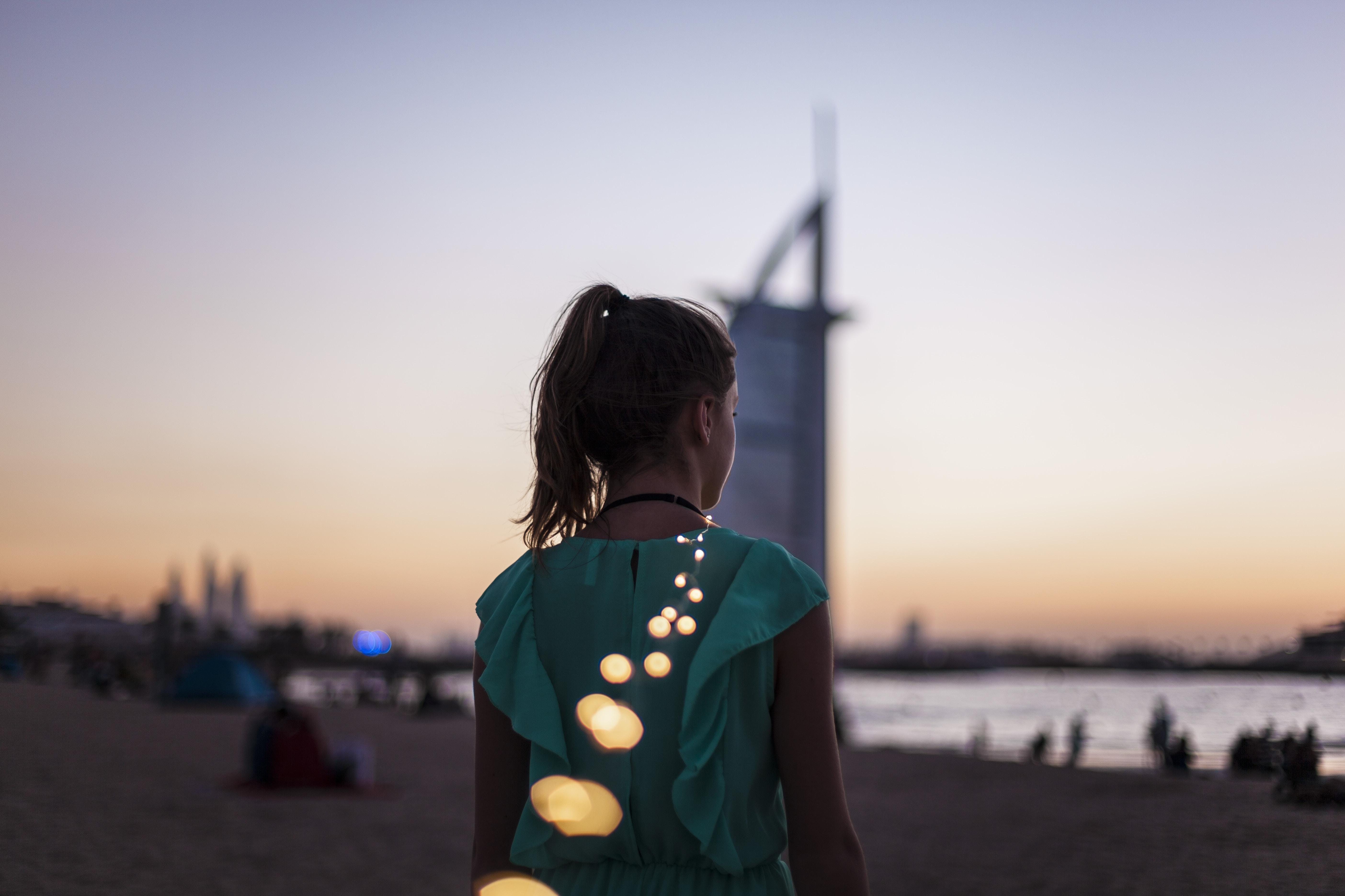 girl standing near Burj Al Arab, Dubai during golden hour