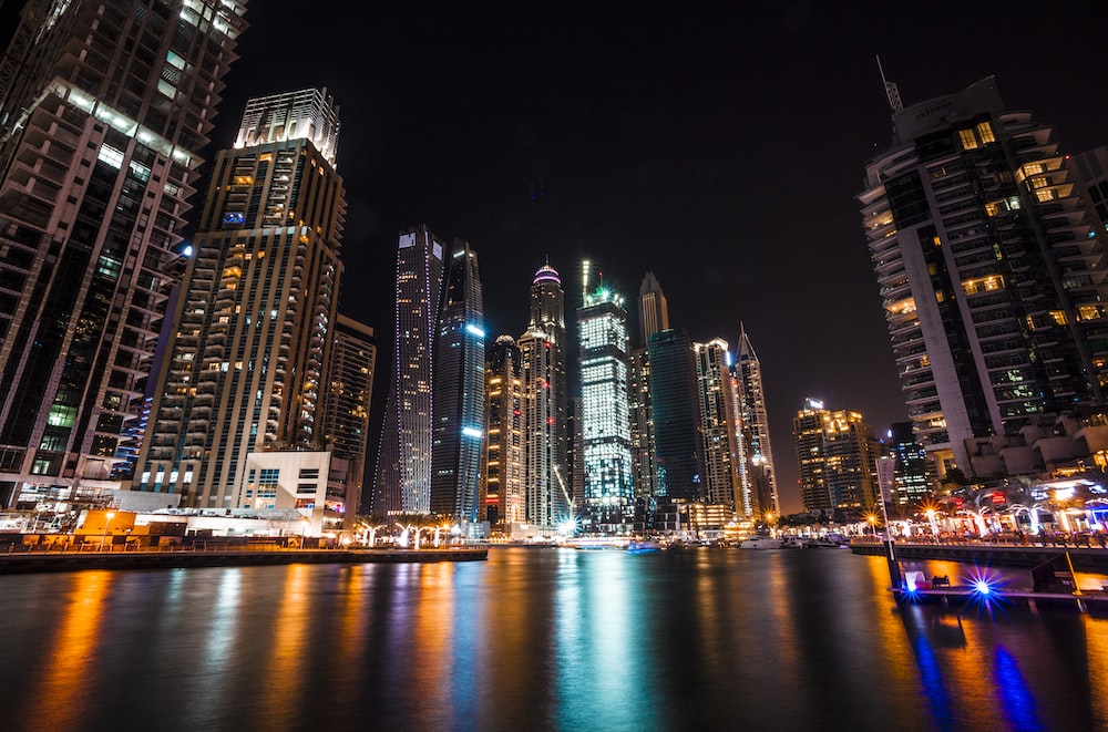 worm's eye view photography of city buildings at night