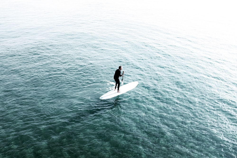 man riding surfboard on body of water
