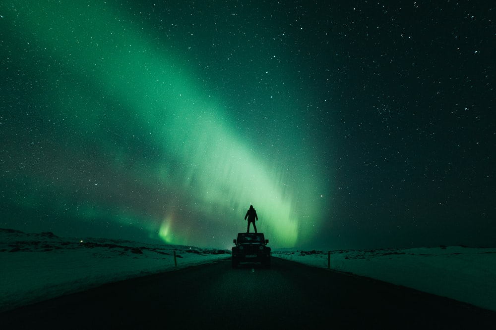 person standing in front of aurora lights