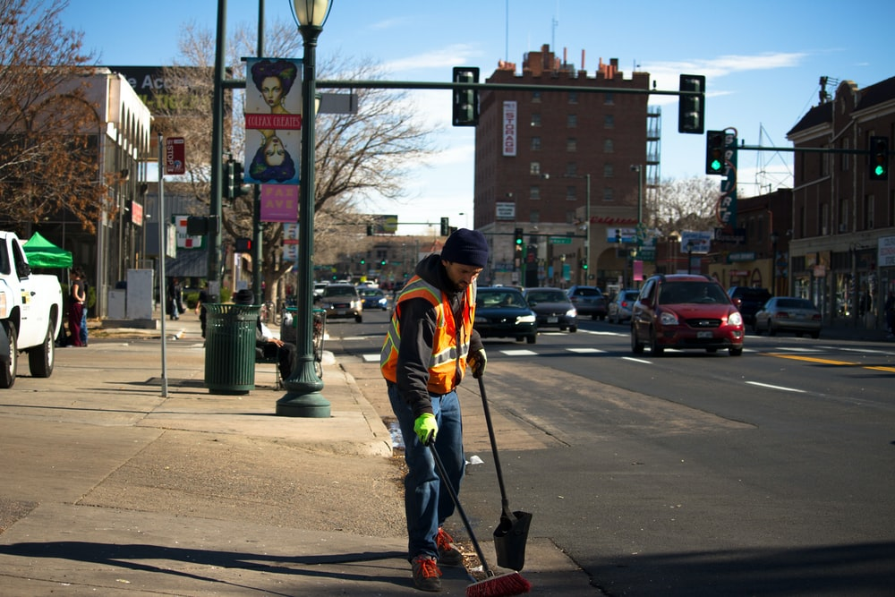 man cleaning the road near traffic light