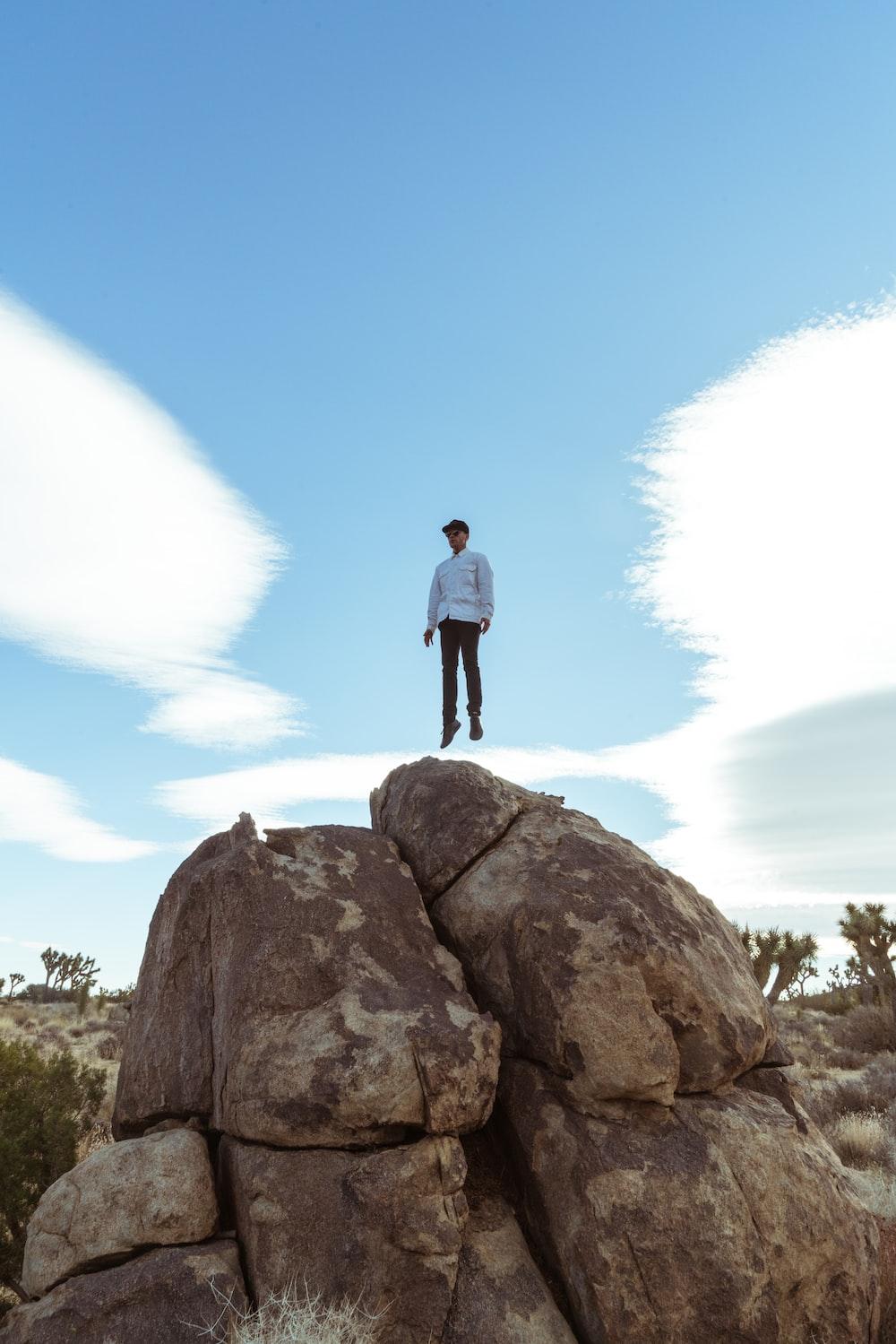 man jump on brown boulder