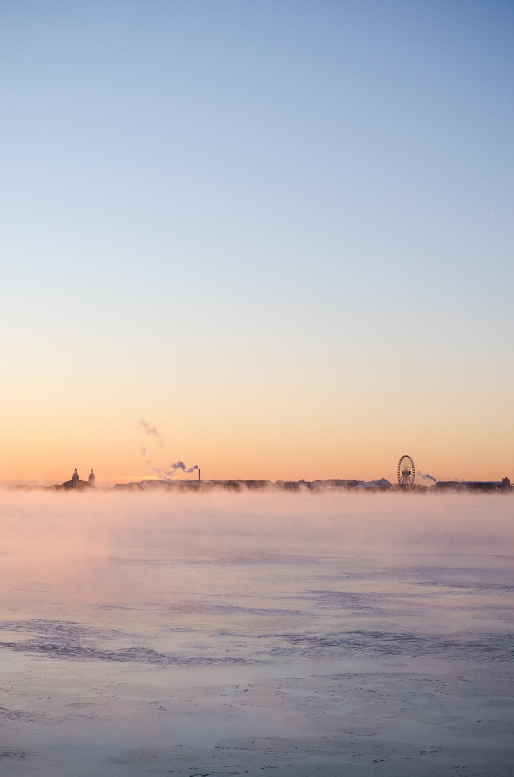ferris wheel standing over the horizon during daytime
