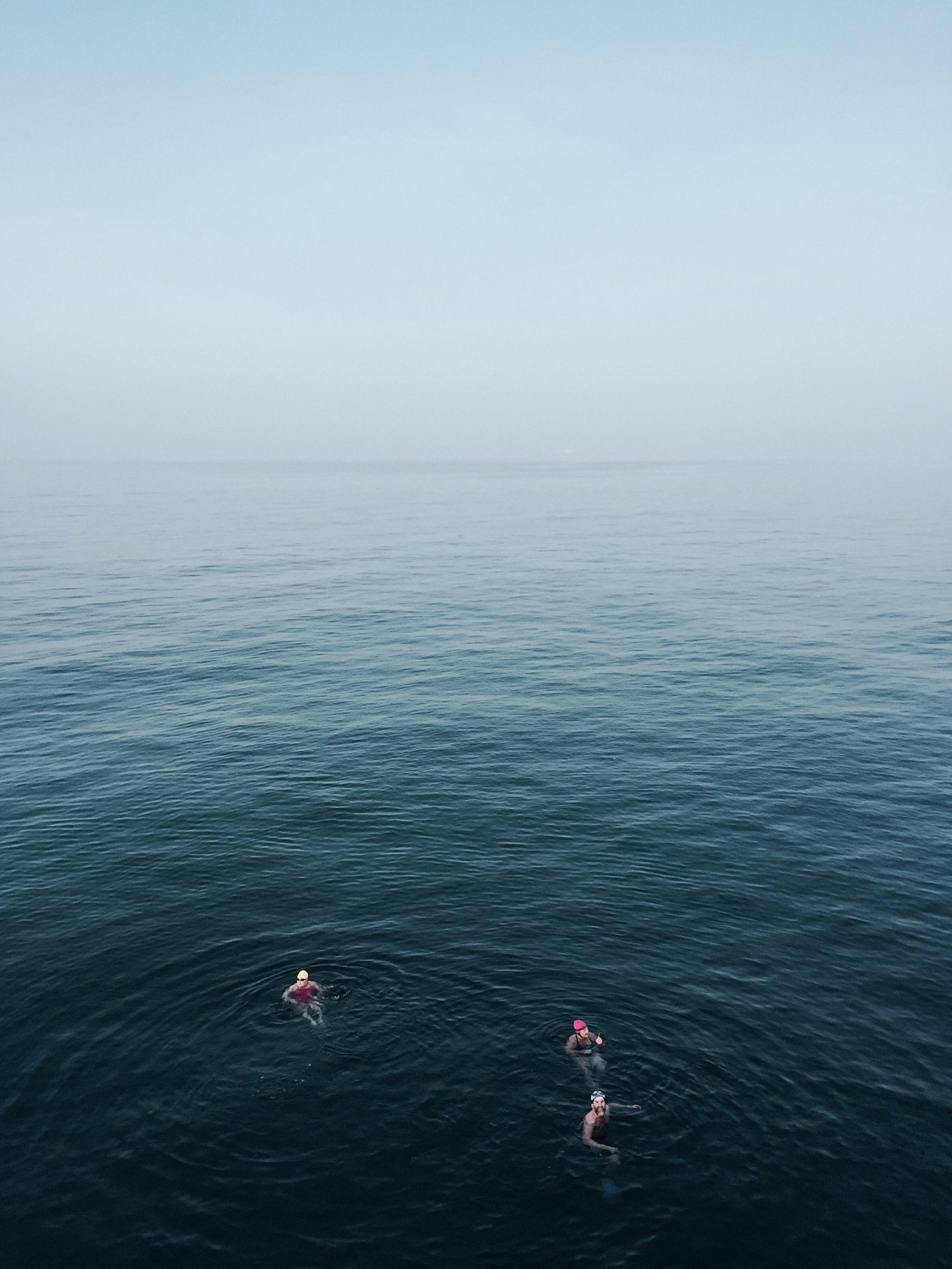 three people floating on body of water