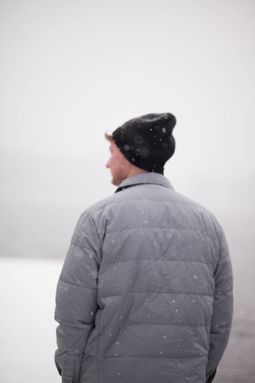 man wearing gray jacket under snow