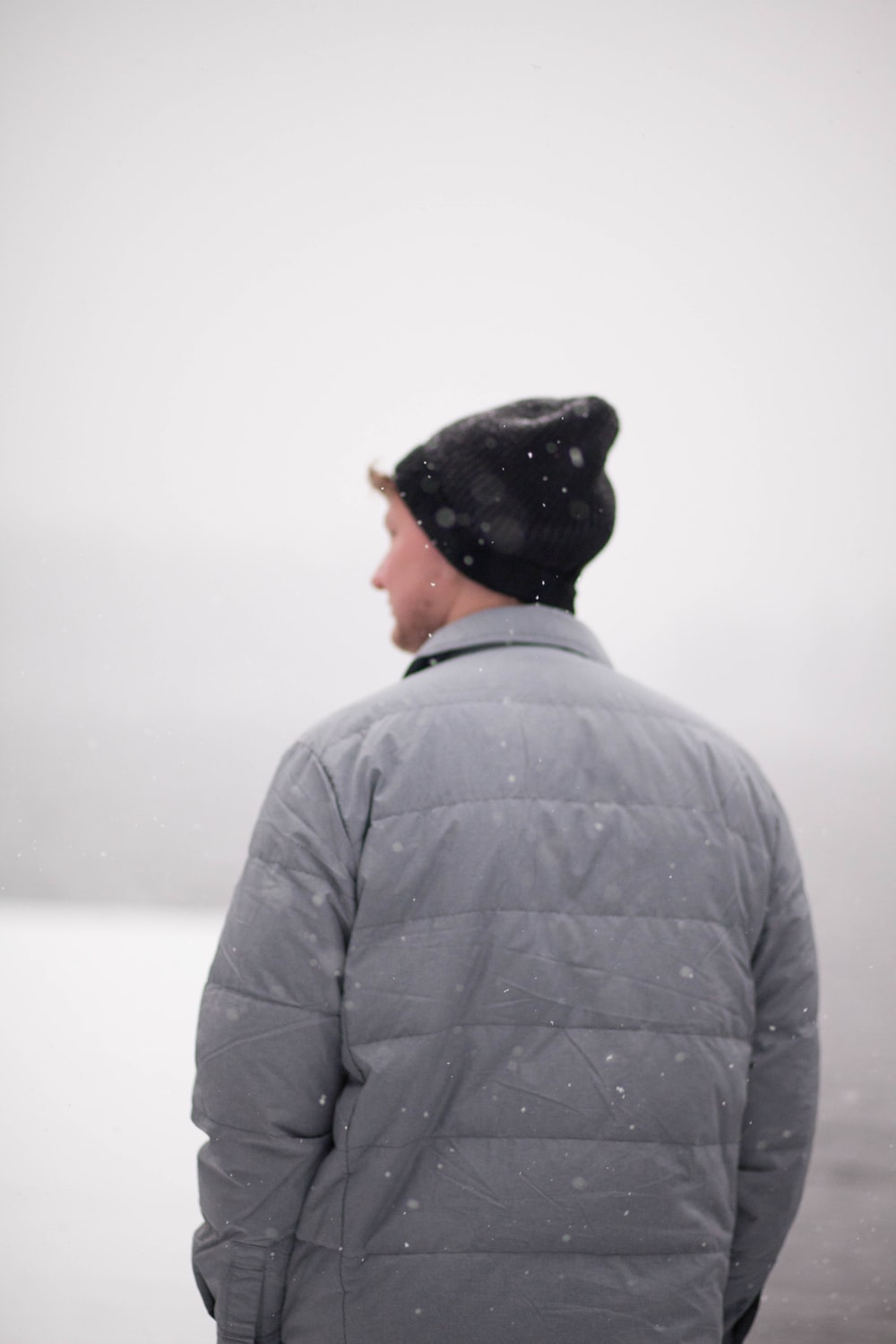man wearing gray jacket under snow