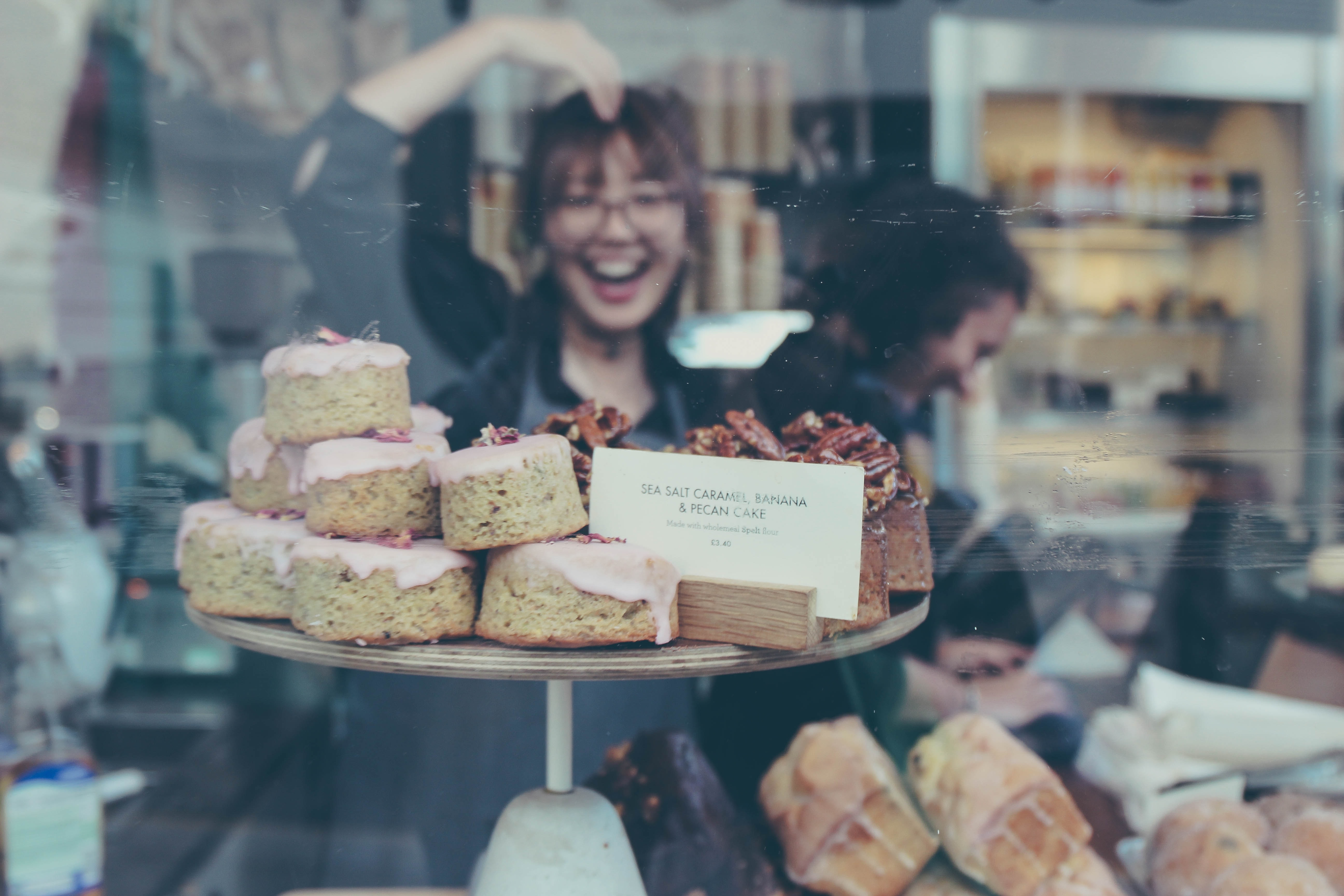 reflection of smiling woman on food display shelf
