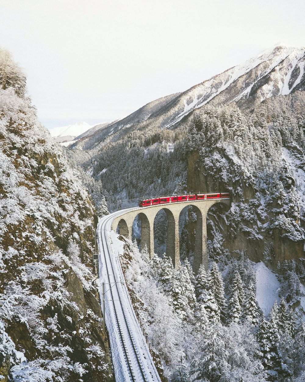 approaching red train across mountains