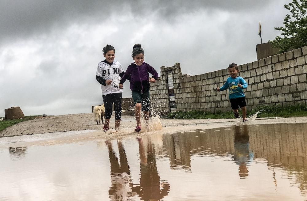 three children running towards body of water