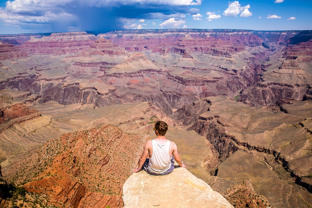 person sitting on cliff during daytime
