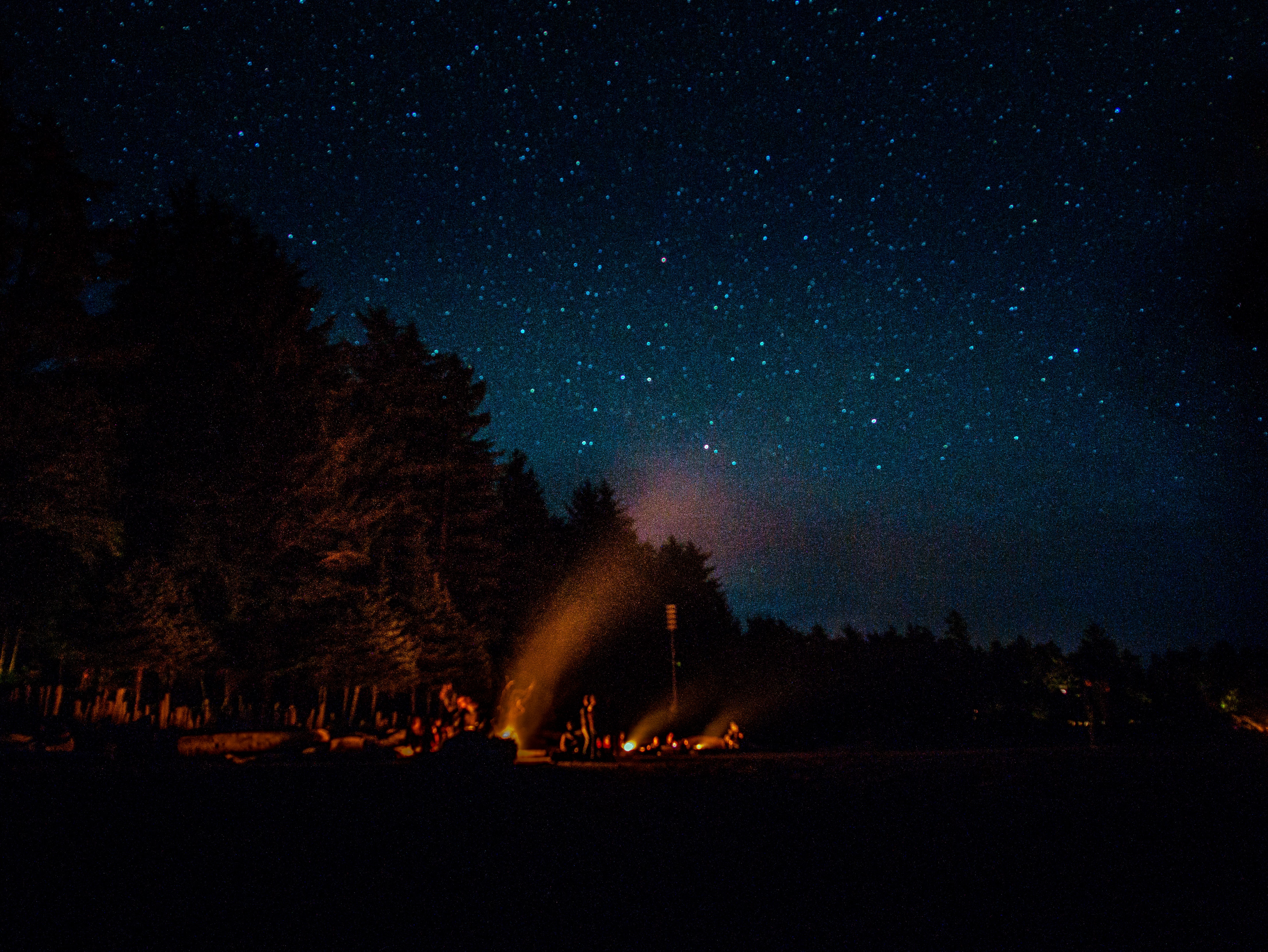 people having bonfire under blue sky filled with stars at night time
