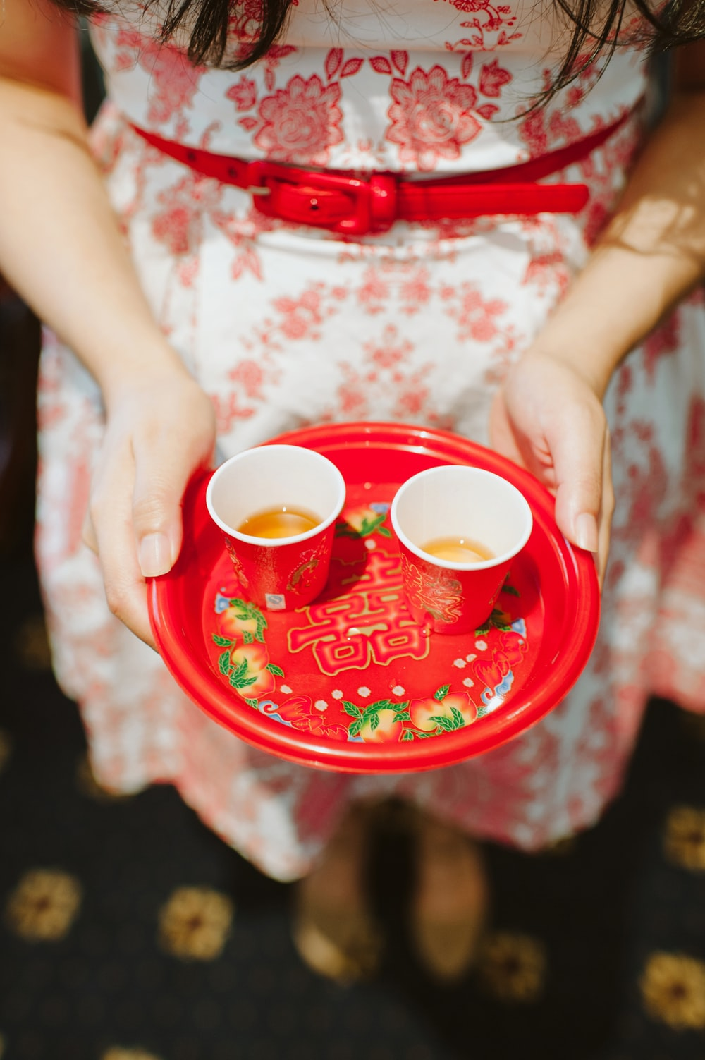 person holding plastic plate with two red cups