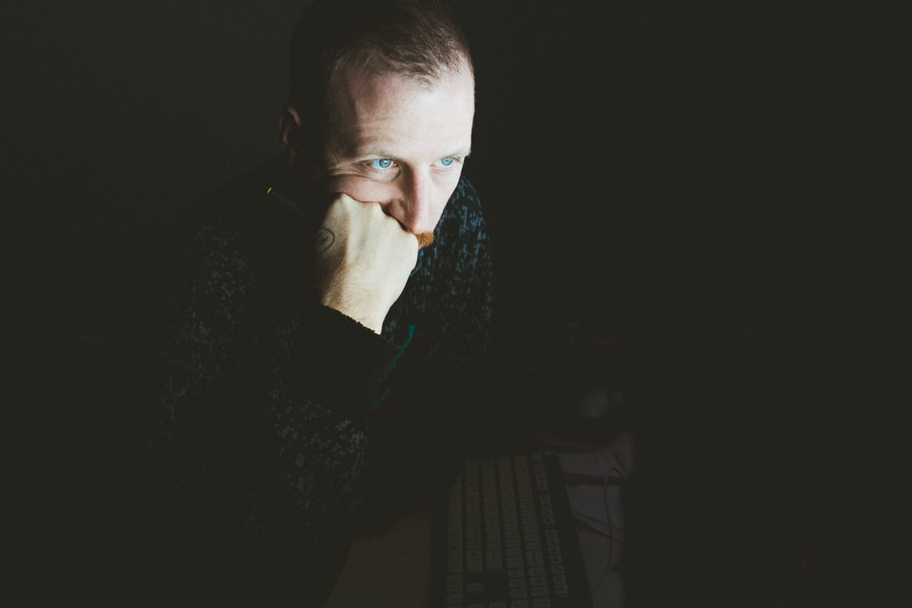 low light photography of man in gray sweater